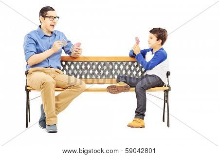 Young boy playing cards with his older cousin seated on bench isolated on white background