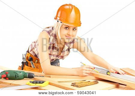 Young female carpenter working and looking at camera isolated on white background