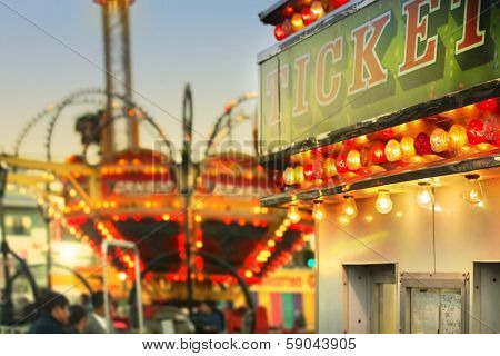 Scene at a classic carnival with a ticket booth in the foreground (focal point on the ticket sign) with overall subtle retro vintage tone and styling