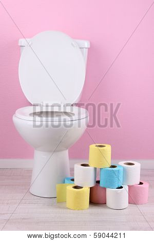 White toilet bowl and colorful rolls of toilet paper, in  bathroom