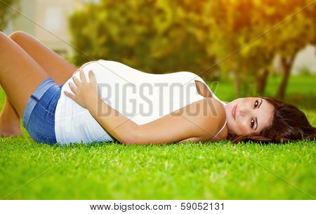 Woman awaiting for a baby, cute pregnant female lying down on fresh green grass in the garden, sunny day, happy and healthy pregnancy concept