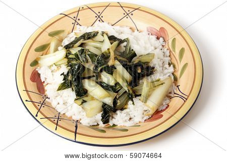 A plate with bok choi asian cabbage chopped and sauteed with sesame oil and soy sauce, served on a bed of white jasmine rice