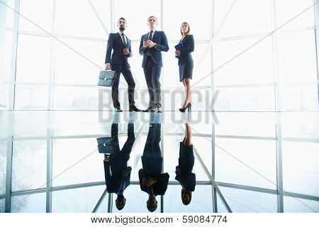 Outlines of successful business partners standing against window in office building