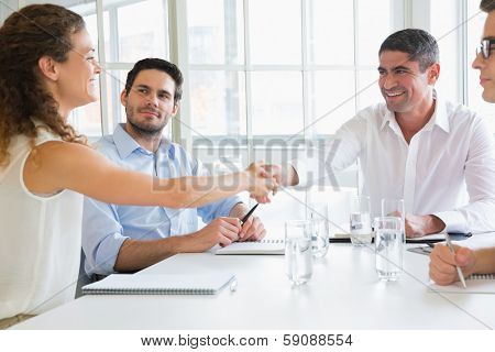 Business partners shaking hands at conference table in office