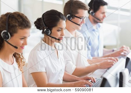 Customer service operators working at desk in office