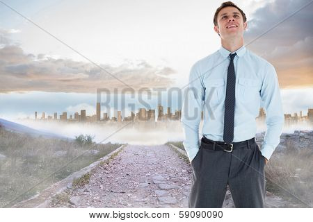 Smiling businessman standing with hand in pocket against rocky path leading to large urban sprawl