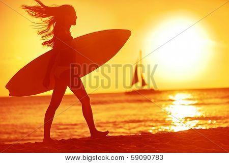 Surfing surfer woman babe beach fun at sunset. Girl walking in sunshine in warm evening sun holding surfboard. Water sport summer vacation travel concept. Kaanapali beach, Maui, Hawaii, USA