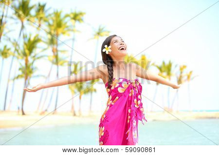 Happy woman praising freedom smiling on hawaiian palm beach in sarong, arms stretched out. Beautiful mixed race female model enjoying sun in worship and meditation zen. Big Island, Hawaii, USA.