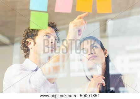 Businessman and businesswoman reading adhesive notes on glass wall in office