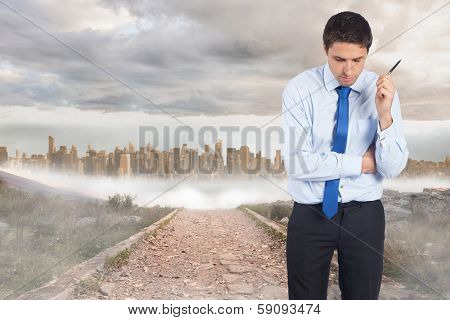 Thinking businessman holding pen against stony path leading to large urban sprawl