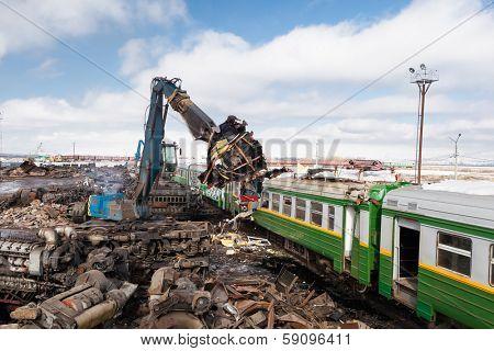 scrap metal machine disassembling a train