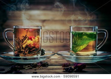Glass cups with tea flower and peppermint tea against wooden background