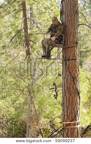 Bow hunter demonstrating good safety technique using a haul line to bring up his bow into a ladder style tree stand