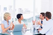 picture of half-dressed  - Smartly dressed young executives sitting around conference table in office - JPG