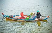 TON LE SAP,CAMBODIA, NOV 22,  2013: Unidentified Cambodian woman rowing her sampan and selling goods