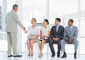 stock photo of beside  - Businessman shaking hands with woman besides people waiting for job interview in a bright office - JPG