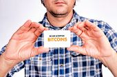 pic of bitcoin  - Man holding card with bitcoins accepting sign - JPG