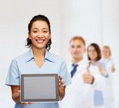 healthcare, medicine and technology concept - smiling african american female doctor or nurse with t