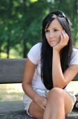 stock photo of beautiful young woman  - Young sad and pensive woman siting on bench in park  - JPG