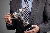 stock photo of trophy  - Businessman celebrating with trophy award for success in business or first place sporting championship win - JPG