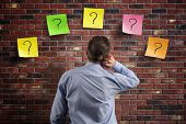 Choice and decisions: businessman thinking with question marks written on adhesive notes stuck to a brick wall poster