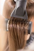 pic of blow-up  - Drying long brown hair with hair dryer and round brush - JPG