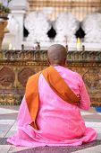 YANGON, MYANMAR - DECEMBER 4, 2013: Buddhist nun praying at the Shwedagon Paya - one of the most imp