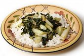 A plate with bok choi asian cabbage chopped and sauteed with sesame oil and soy sauce, served on a b