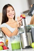 Woman making apple and vegetable juice on juicer machine at home in kitchen. Juicing and healthy eat