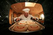 picture of pie-in-face  - A Man bakes his signature Smiley Face Cookies in his oven for his hungry family and friends - JPG