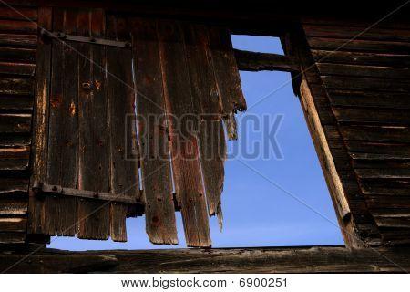 Damaged Old Barn Wood Door Over Blue Sky