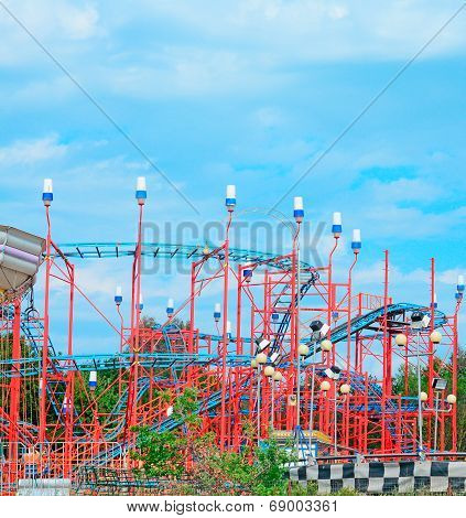 Red Roller Coaster Under A Blue Sky