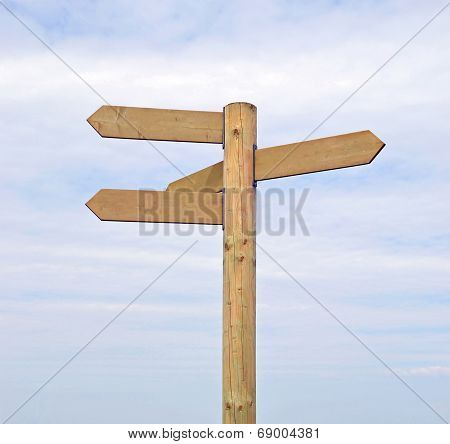 A wooden signpost against a sky background