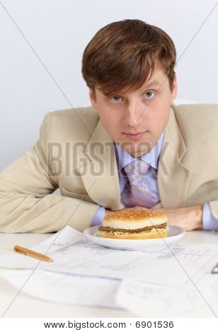 Young Man In A Light Jacket And Big Sandwich