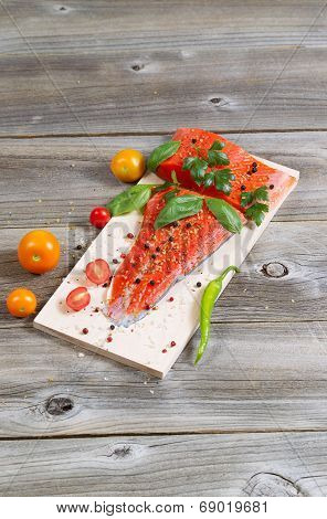 Wild Salmon And Ingredients On Wooden Plank For Cooking