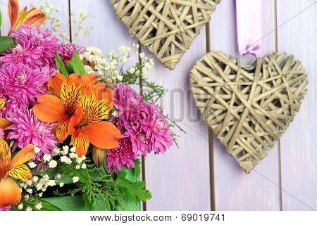 Flowers composition in crate with decorative heart on wooden background