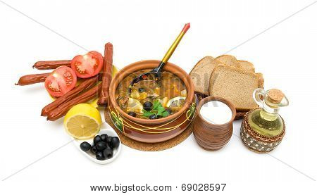 Dish Of Russian Hodgepodge Soup In Ceramic Pot And Other Foodstuffs On White Background