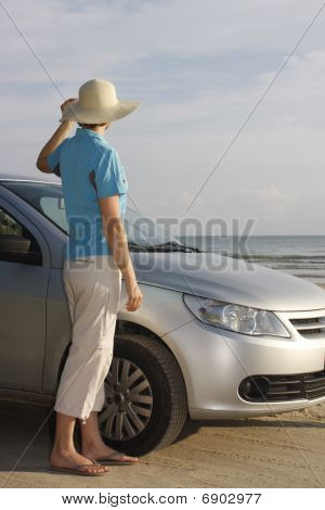 Woman Standing Beside A Car On A Beach