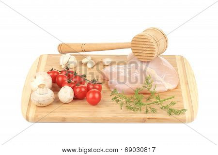 Chicken breast and vegetables with meat mallet.