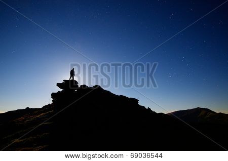Night landscape with the starry sky. Moonlight over a man standing on a rock
