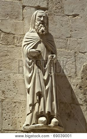 Ancient cleric statue on the side facade of Santa Maria Maggiore church, Caramanico Terme, Abruzzo region, Italy