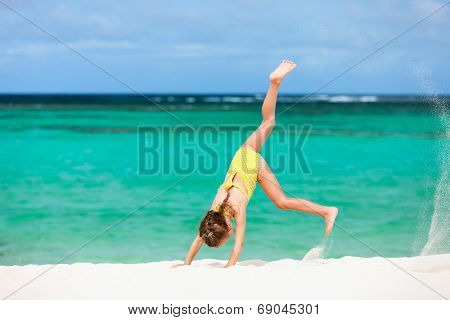 Cute little girl having fun making cartwheel and enjoying vacation on tropical beach with white sand and turquoise ocean water