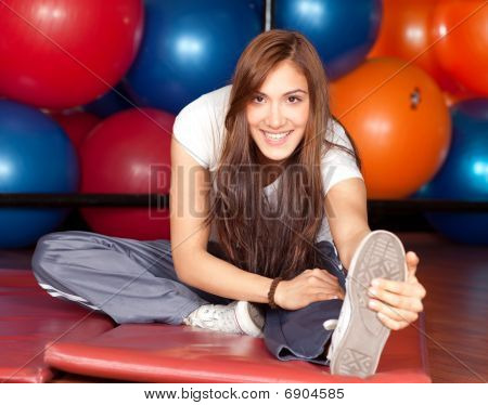 Happy Young Women Stretching In The Gym