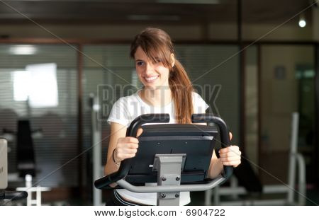 Happy Young Woman In The Gym Biking