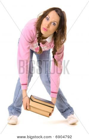 Student Holding Heavy Pile Of Books