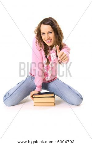 Student Sitting On Pile Of Books And Showing Thumbs Up