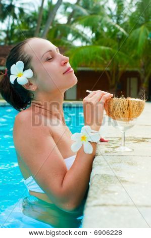 Woman In Pool With Coconut Cocktail