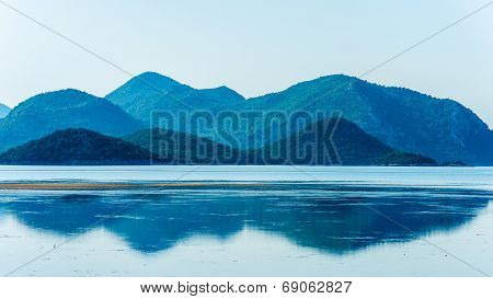 Calm Sea With Distant Mountains And Reflection In Water