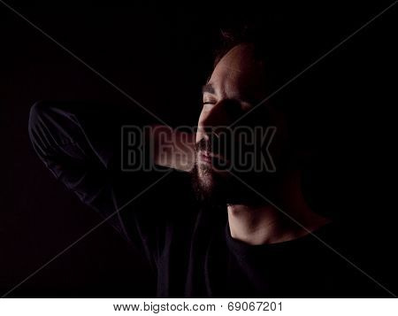 Low Key Image Of A Bearded Man With A Sore Neck