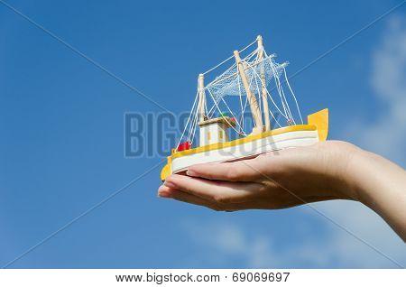 Wooden Ship Toy On Palm On Blue Sky Background